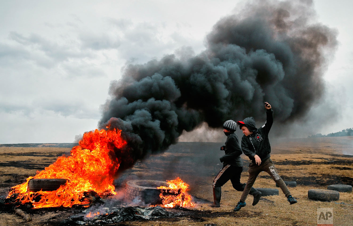 Children jump after pushing a burning tire during a ritual marking the upcoming Clean Monday, the beginning of the Great Lent, 40 days ahead of Orthodox Easter, on the hills surrounding the village of Poplaca, in central Romania's Transylvania region, Sunday, March 10, 2019. (AP Photo/Vadim Ghirda)