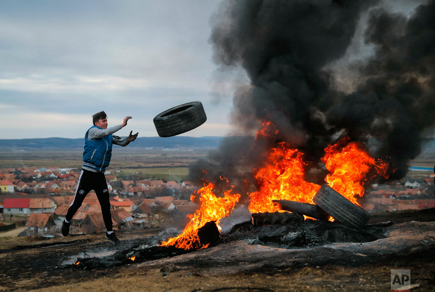 A young man throws a tire during a ritual marking the upcoming Clean Monday, the beginning of the Great Lent, 40 days ahead of Orthodox Easter, on the hills surrounding the village of Poplaca, in central Romania's Transylvania region, Sunday, March 10, 2019. (AP Photo/Vadim Ghirda)