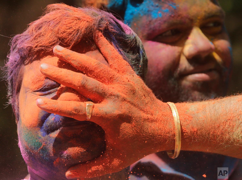 Revelers smear colored powder on a man during celebrations marking Holi, the Hindu festival of colors, in Mumbai, India, March 21, 2019. (AP Photo/Rajanish Kakade)