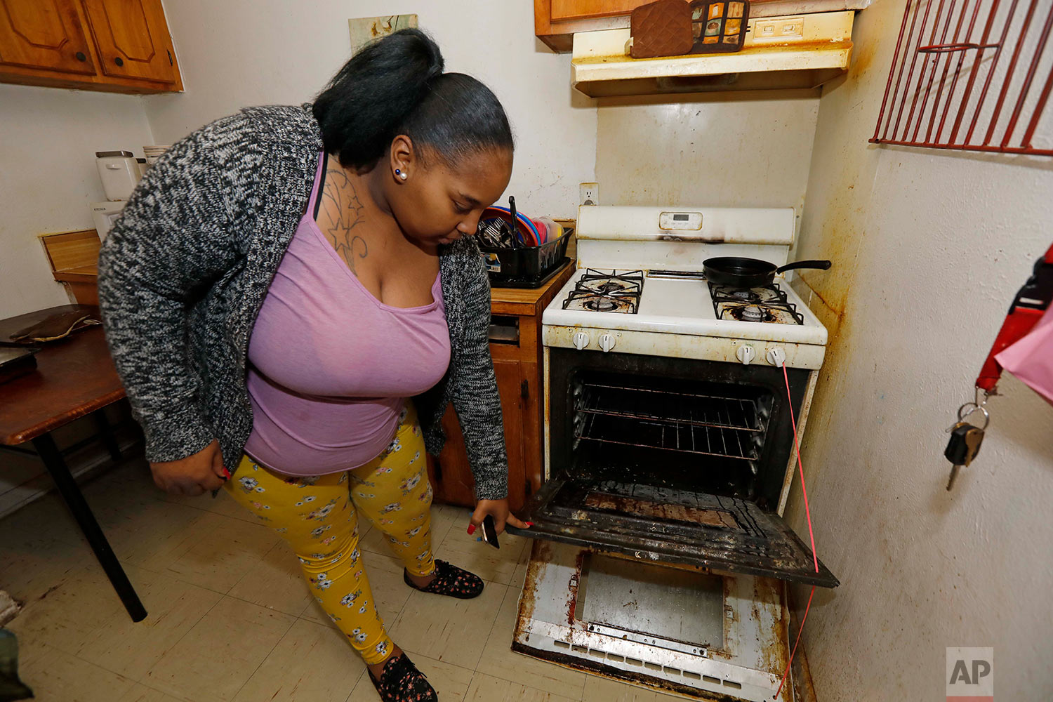 In this Feb. 20, 2019 photo, Destiny Johnson shows the broken door to her oven that she uses string to hold together, in her apartment in Cedarhurst Homes, a federally subsidized, low-income apartment complex in Natchez, Miss. The complex failed a health and safety inspection in each of the past three years. Upset with conditions, Johnson moved out in late March. (AP Photo/Rogelio V. Solis)