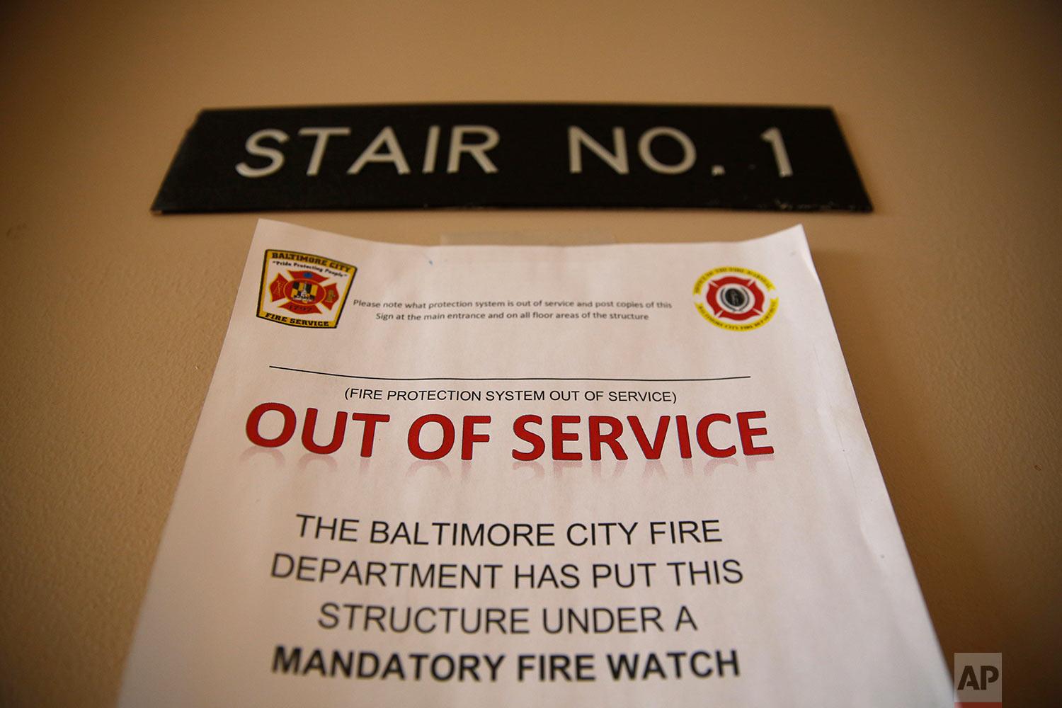 In this Feb. 22, 2019 photo, a sign alerts residents in Rosemont Tower in Baltimore that the fire sprinkler system is out of service, requiring a firefighter to stand watch around the clock. (AP Photo/Patrick Semansky)