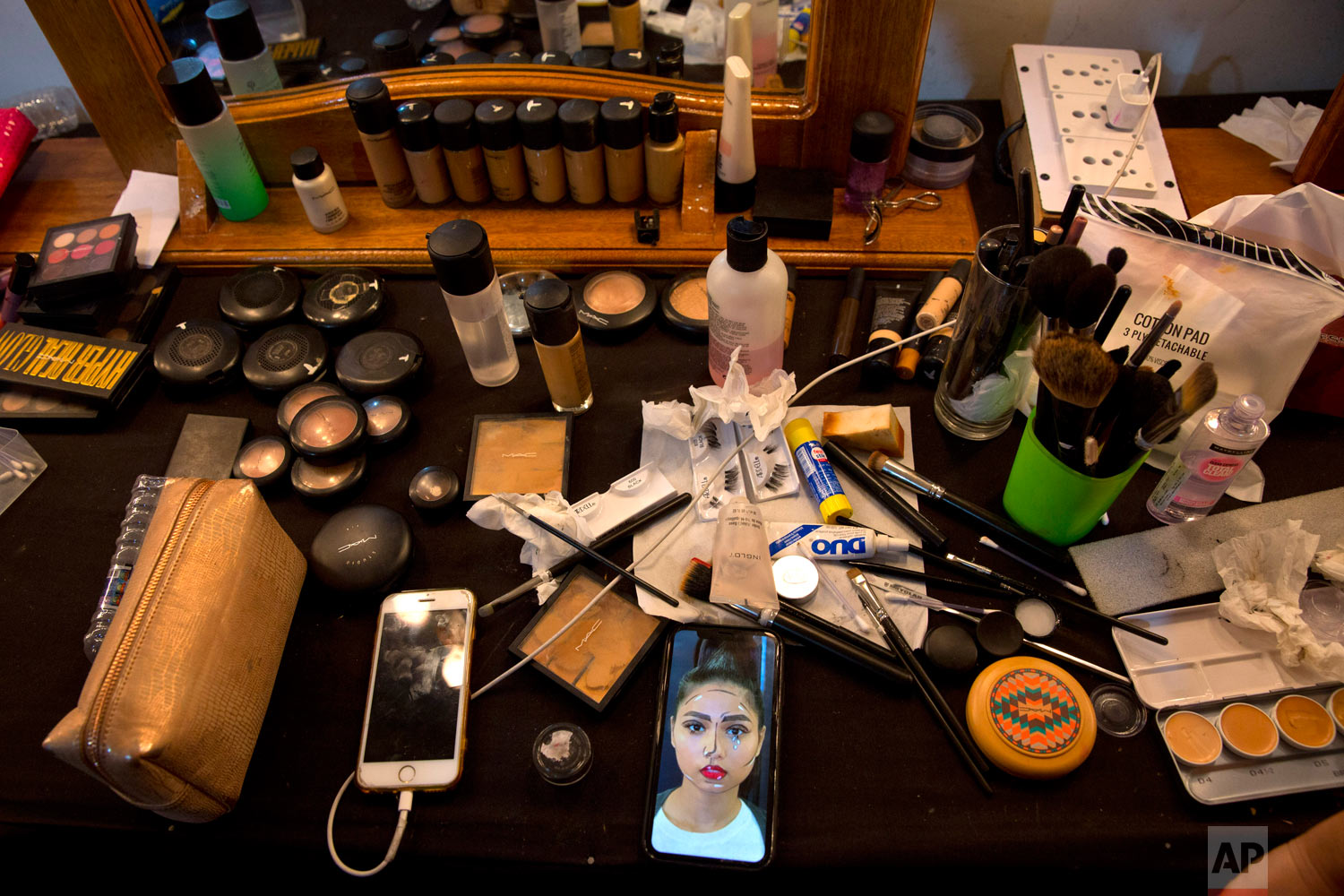 A photograph of an Indian model is seen on the mobile phone of a makeup artist at the main makeup room at the Lotus Makeup India Fashion Week, Thursday, March 14, 2019, in New Delhi, India. (AP Photo/Manish Swarup)