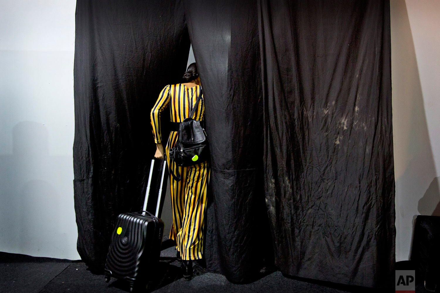 A model leaves the changing area after showcasing creations of Indian designers for the Lotus Makeup India Fashion Week, on Thursday, March 14, 2019, in New Delhi, India. (AP Photo/Manish Swarup)