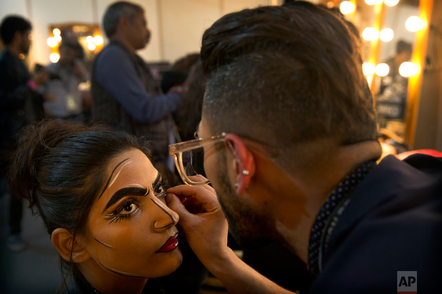 A makeup artist applies eyeliner to a model before a show at the Lotus Makeup India Fashion Week, on Thursday, March 14, 2019, in New Delhi, India. (AP Photo/Manish Swarup)