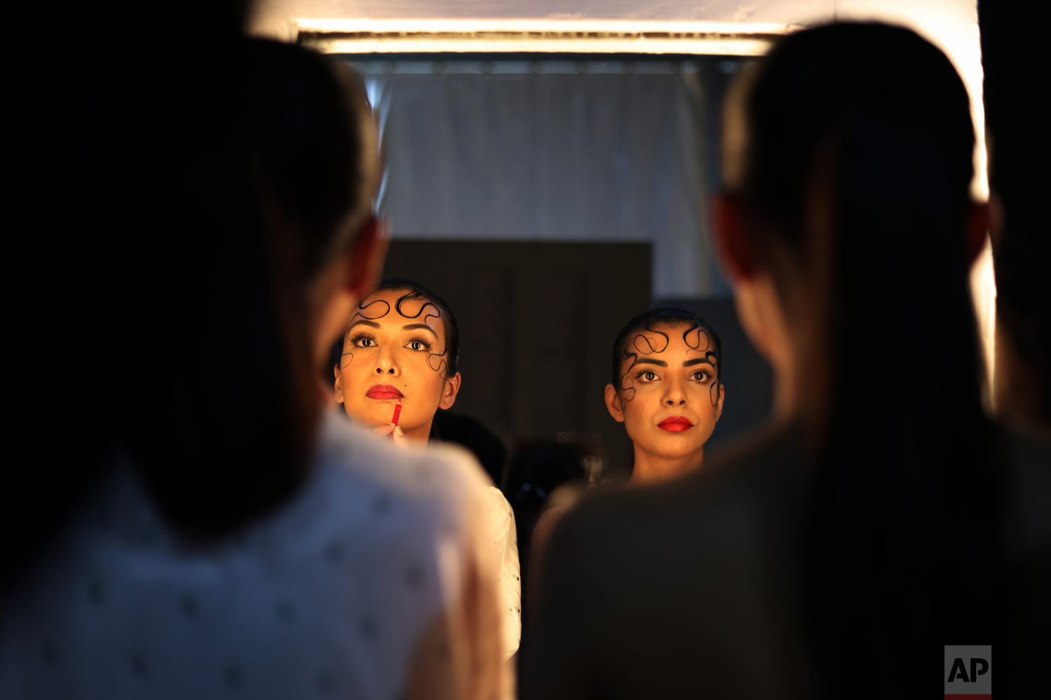 Models finish applying their makeup before taking to the runway at the Lotus Makeup India Fashion Week, on Wednesday, March 13, 2019, in New Delhi, India. (AP Photo/Manish Swarup)
