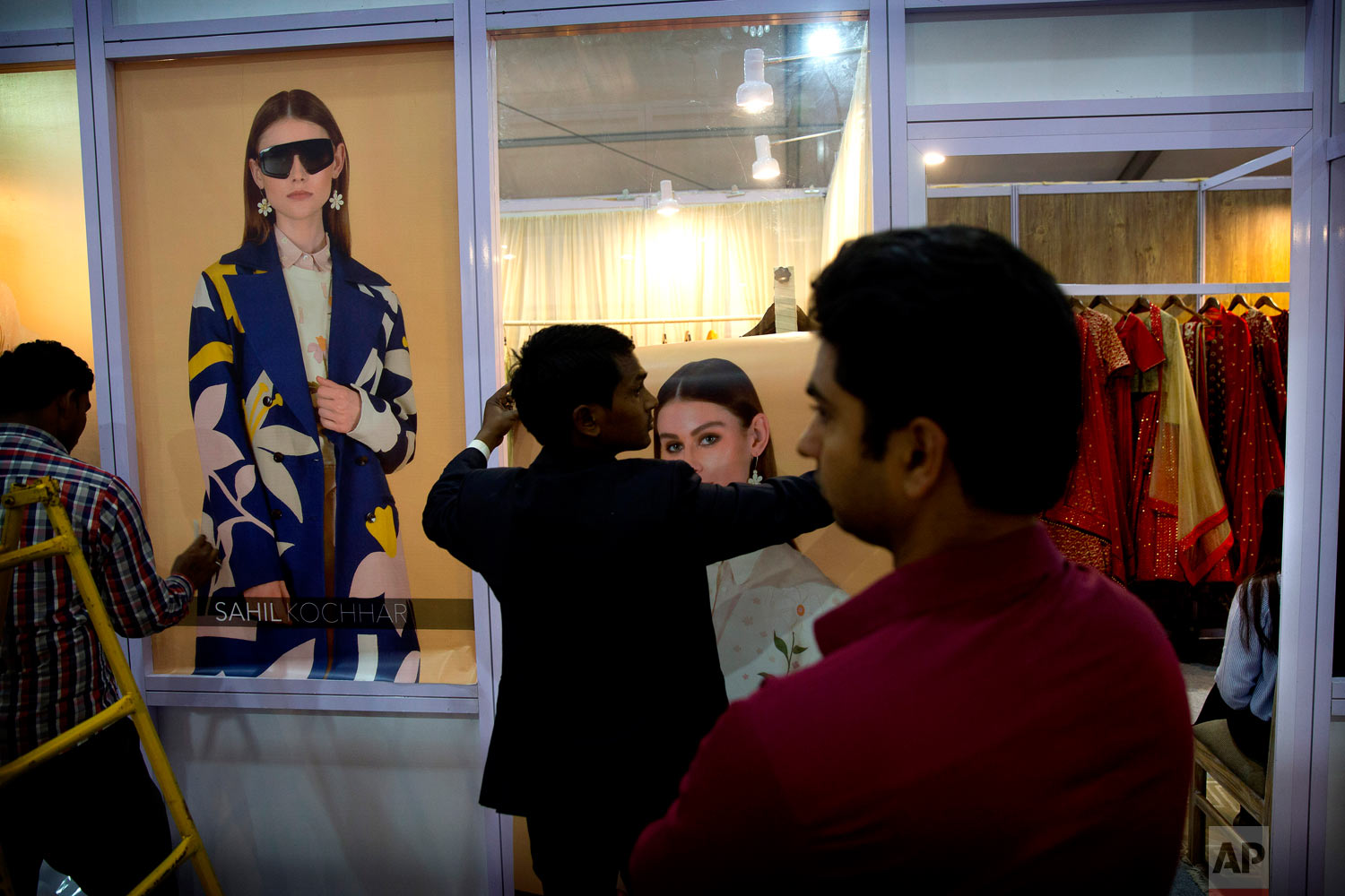 Workers put up posters of models outside a fashion designer's stall in an exhibition during Lotus Makeup India Fashion Week, Wednesday, March 13, 2019, in New Delhi, India. (AP Photo/Manish Swarup)
