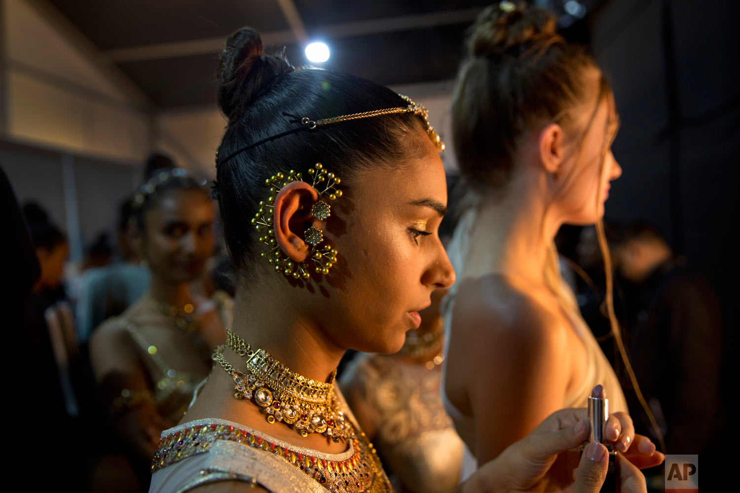 A models touches up her makeup before walking the ramp during Lotus Makeup India Fashion Week, on Saturday, March 16, 2019, in New Delhi, India. (AP Photo/Manish Swarup)