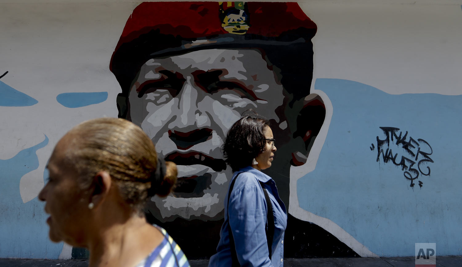 "Pedestrians walk past a mural featuring Venezuela's late President Hugo Chavez, in Caracas, Venezuela, Tuesday, March 19, 2019. Chavez, a former military officer, declared a socialist ""revolution"" after coming to power in 1999. He was succeeded after his 2013 death by his protege, Nicolas Maduro. (AP Photo/Natacha Pisarenko)"