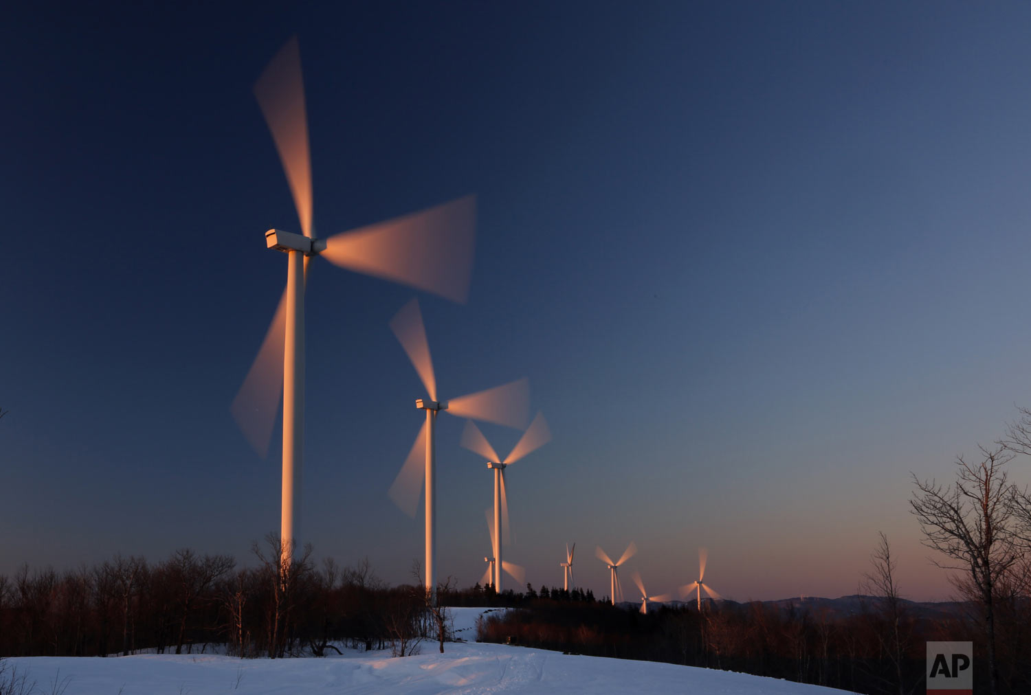 Wind turbines are bathed in the first rays of sunlight at the Saddleback Ridge Wind Project, Wednesday, March 20, 2019, in Carthage, Maine. The first day of spring blew in with gentle winds and cold temperatures. Warmer and wetter weather is expected later in the week. (AP Photo/Robert F. Bukaty)