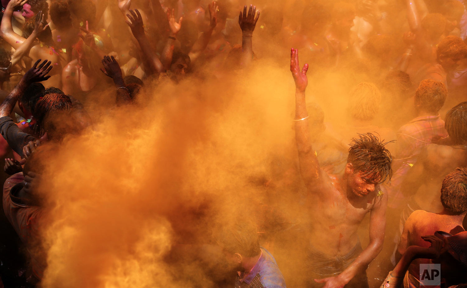 Revelers dance as colored powders are sprayed during celebrations for the Hindu festival Holi in Prayagraj, India, on Friday, March 22, 2019. The riotous annual celebration of color, marks the end of winter and the arrival of spring. People armed with water balloons, colored water and powder in multiple hues played Holi by smearing each other's faces with color. (AP Photo/ Rajesh Kumar Singh)