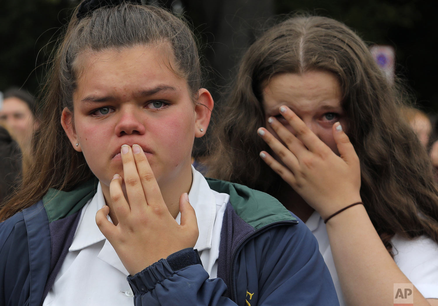 Students react as they gather for a vigil to commemorate victims of the shootings, outside the Al Noor mosque in Christchurch, New Zealand, Monday, March 18, 2019. (AP Photo/Vincent Yu)