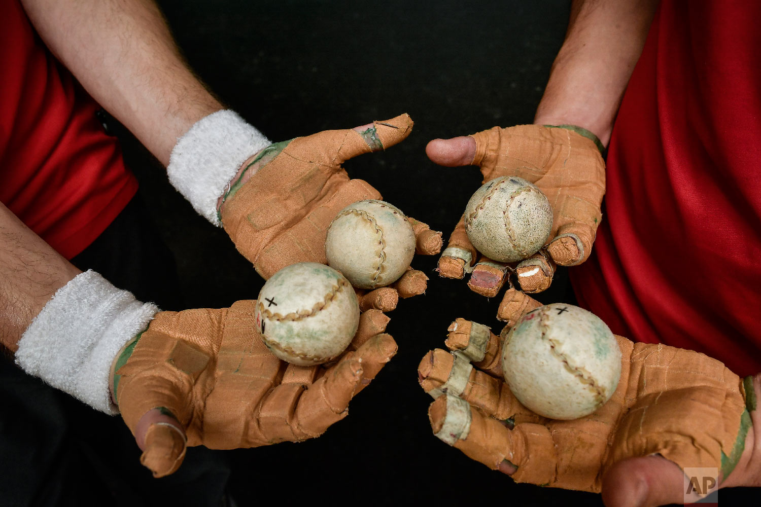 Players of Basque Ball hold balls on their hands protected by layers of tightly-bound tape, in Pamplona, northern Spain on March 5, 2019. (AP Photo/Alvaro Barrientos)