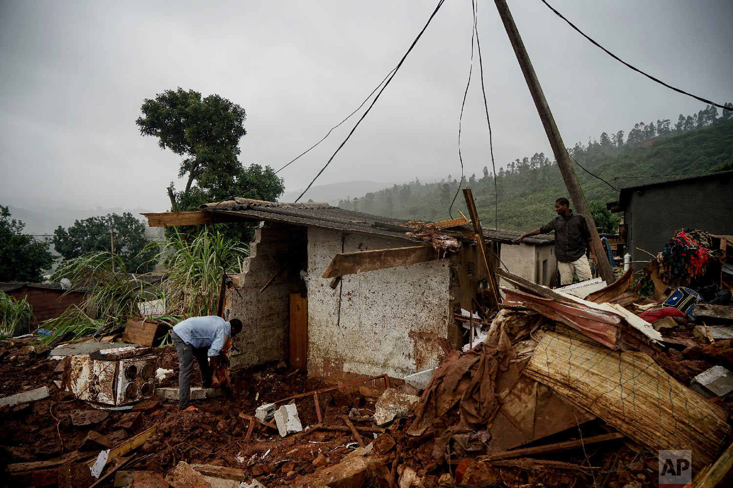 Men search to salvage what they can from a house which was damaged by Cyclone Idai in Chimanimani, Zimbabwe, Saturday, March 23, 2019 after Cyclone Idai caused floods that swept through Mozambique, Zimbabwe and Malawi. (AP Photo/KB Mpofu)