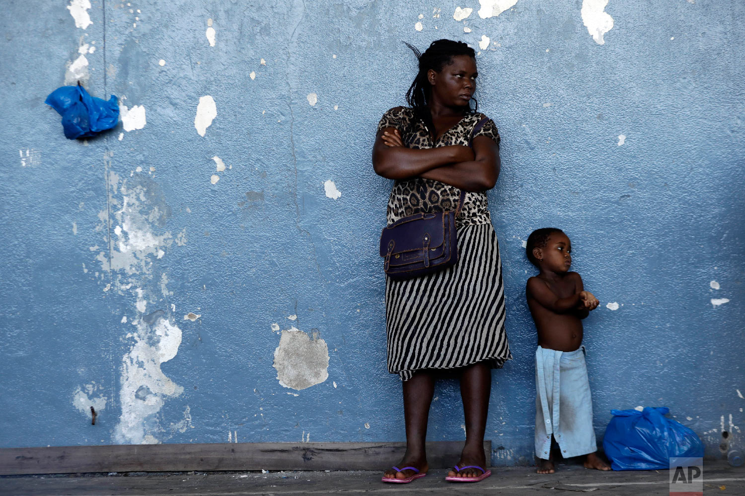 A woman and her child send against the wall at a displacement centre in Beira, Mozambique, Friday, March 22, 2019. (AP Photo/Themba Hadebe)