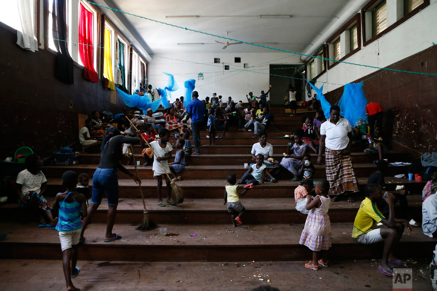 Displaced families victims of Cyclone Idai, eat lunch at the Samora Machel Secondary School which is being used to house victims of the floods in Beira, Mozambique, Sunday March 24, 2019. (AP Photo/Phill Magakoe)