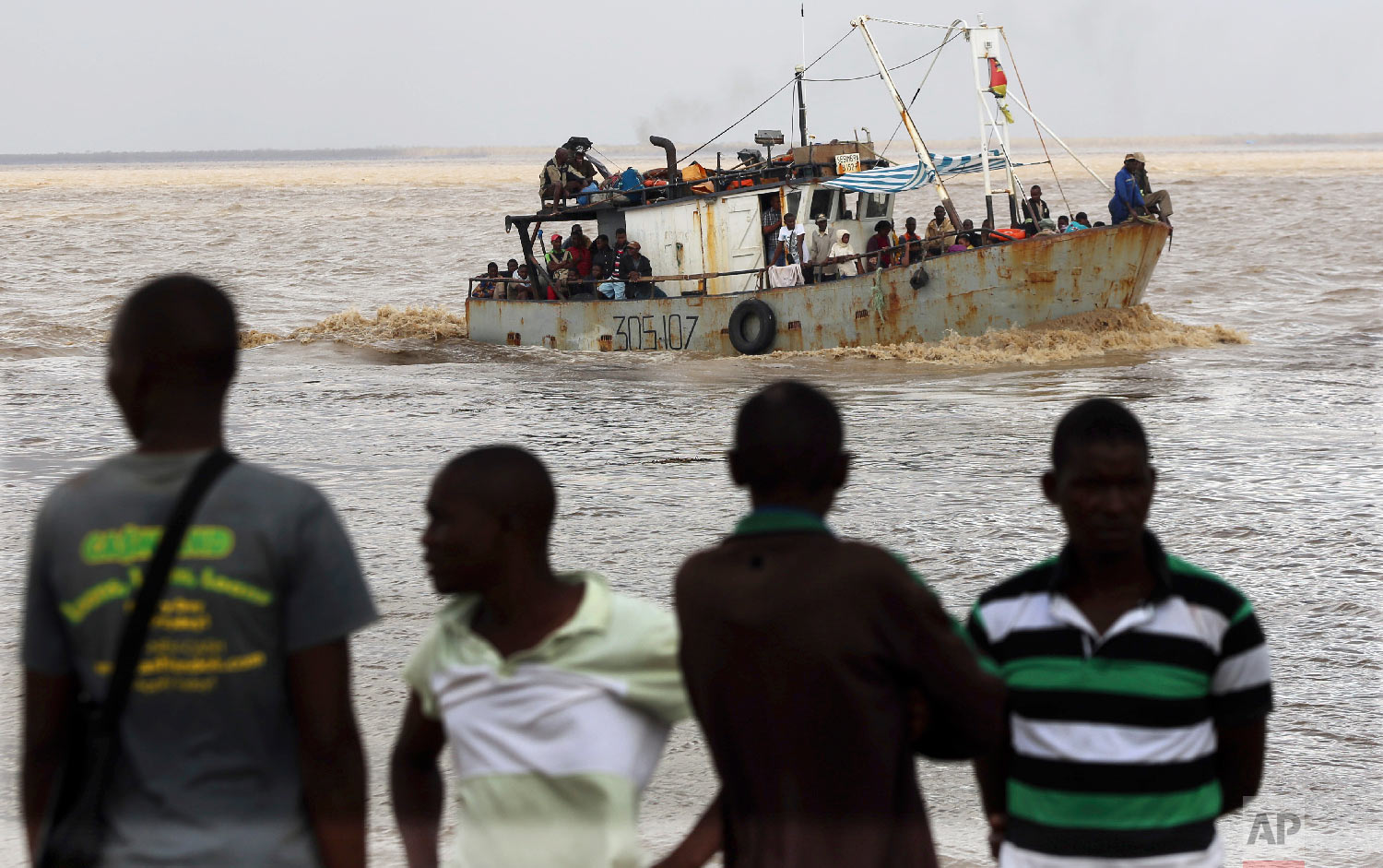 A group of men watch the arrival of a boat carrying displaced families rescued from a flooded area of Buzi district, 200 kilometers (120 miles) outside Beira, Mozambique, on Saturday, March 23, 2019. (AP Photo/Themba Hadebe)
