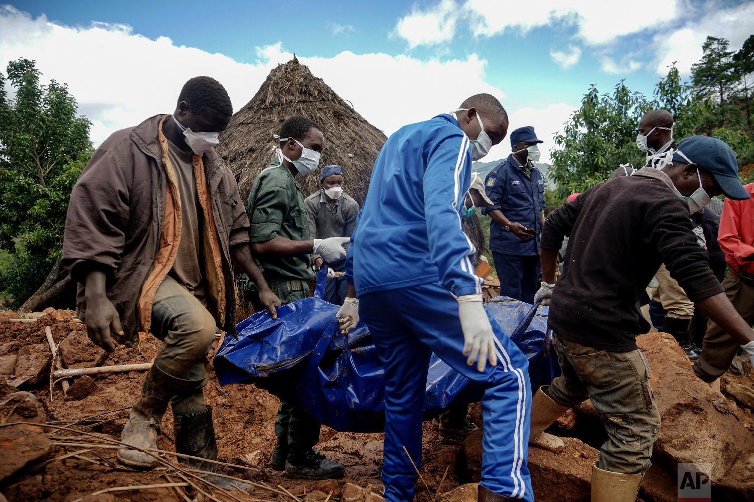 Men retrieve the body of 17-year-old Agreement Munanga, who died last Friday after Cyclone Idai caused mudslides in Chimanimani, Zimbabwe, Friday, March 22, 2019. (AP Photo/KB Mpofu)