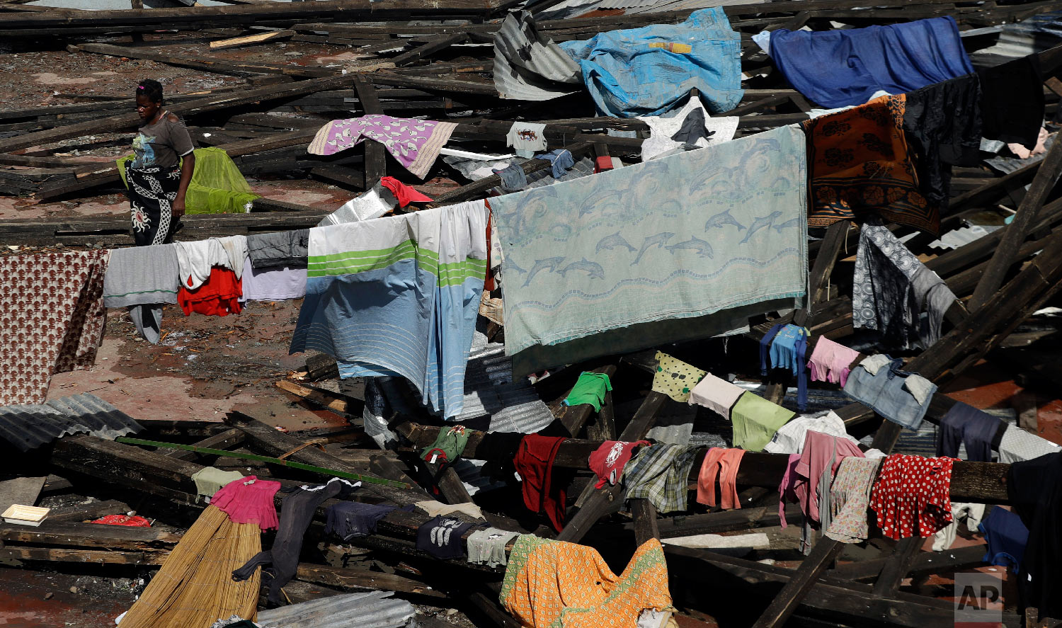 A woman hangs a her wet clothes at a displacement center in Beira, Mozambique, Friday, March 22, 2019. (AP Photo/Themba Hadebe)