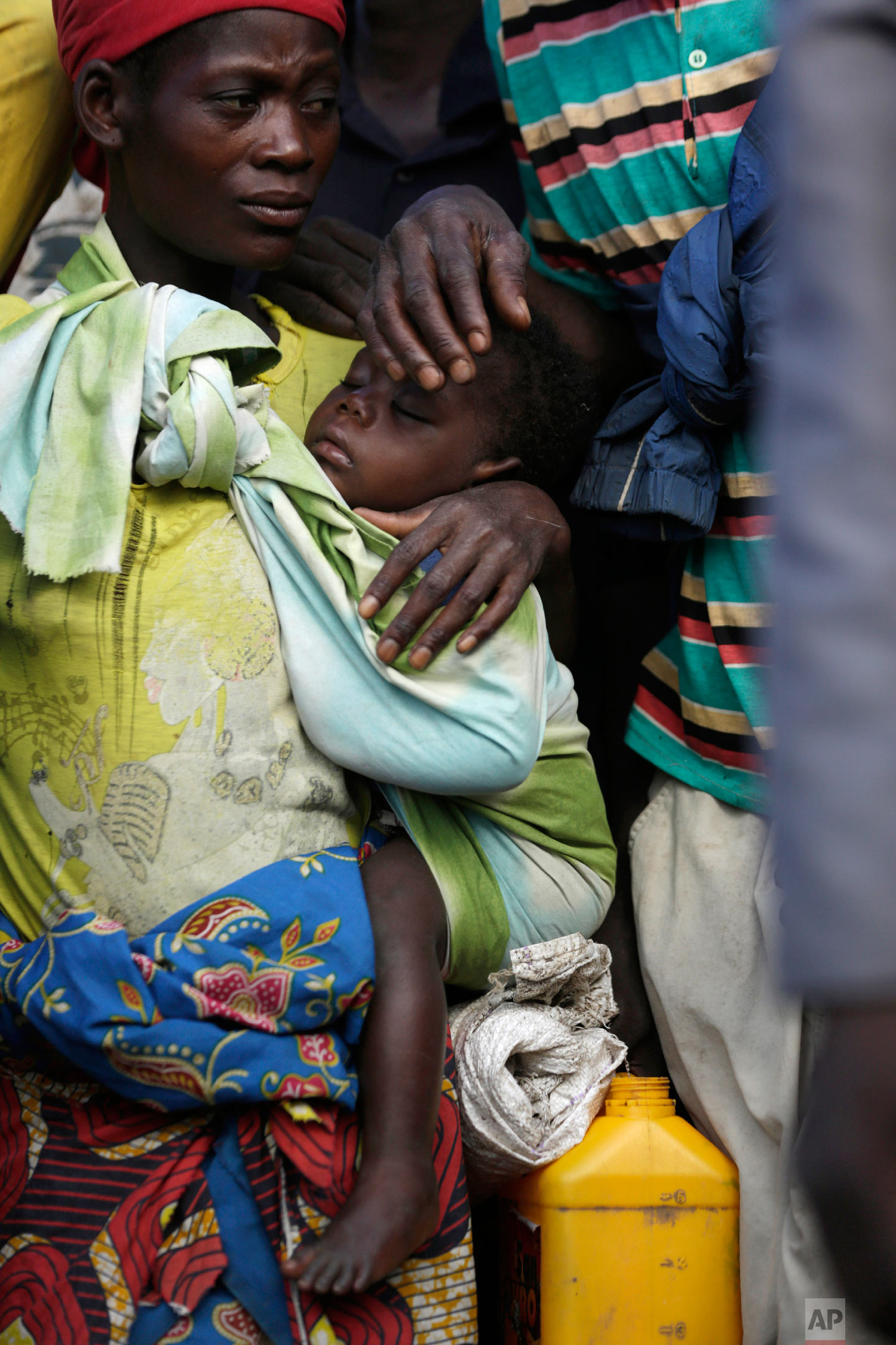 A woman carrying her child stands in a queue to receive food from World Food Programme in Nhamatanda, about 100km west of Beira, Mozambique Thursday, March 21, 2019. (AP Photo/Themba Hadebe)