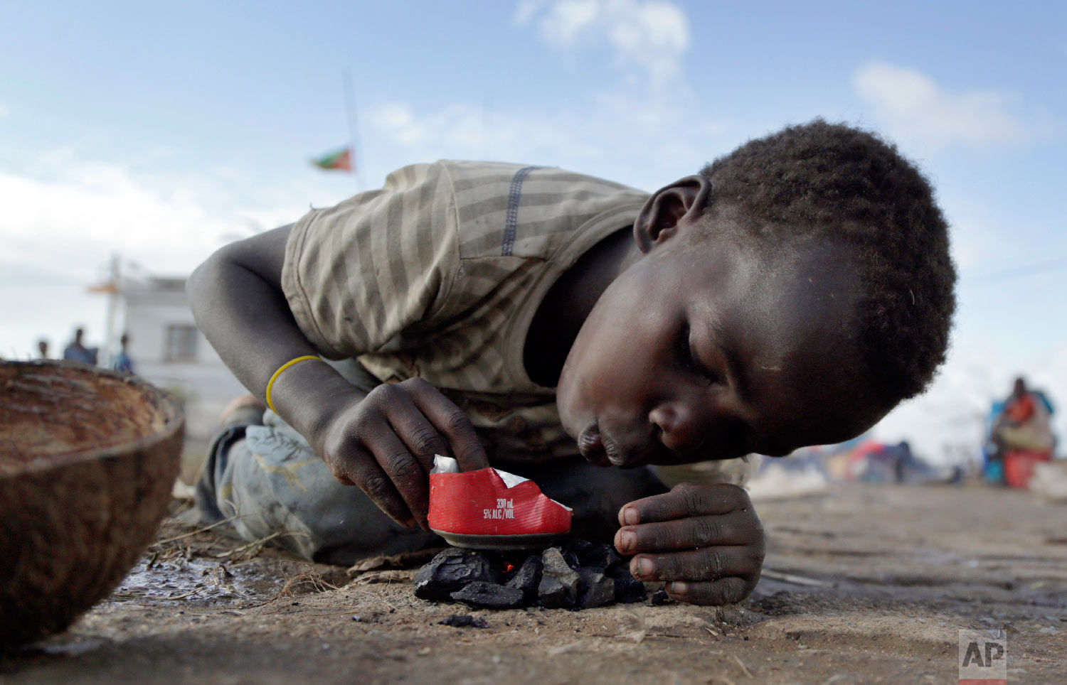 A young boy makes fire as he plays in Buzi district, 200 kilometers (120 miles) outside Beira, Mozambique, on Saturday, March 23, 2019. (AP Photo/Themba Hadebe)
