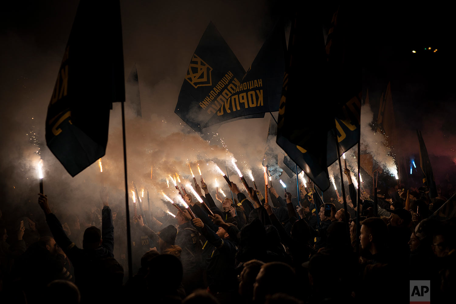 Members of nationalist movements light flares during a rally marking Defender of Ukraine Day in Kiev, Ukraine, Oct. 14, 2018. (AP Photo/Felipe Dana)
