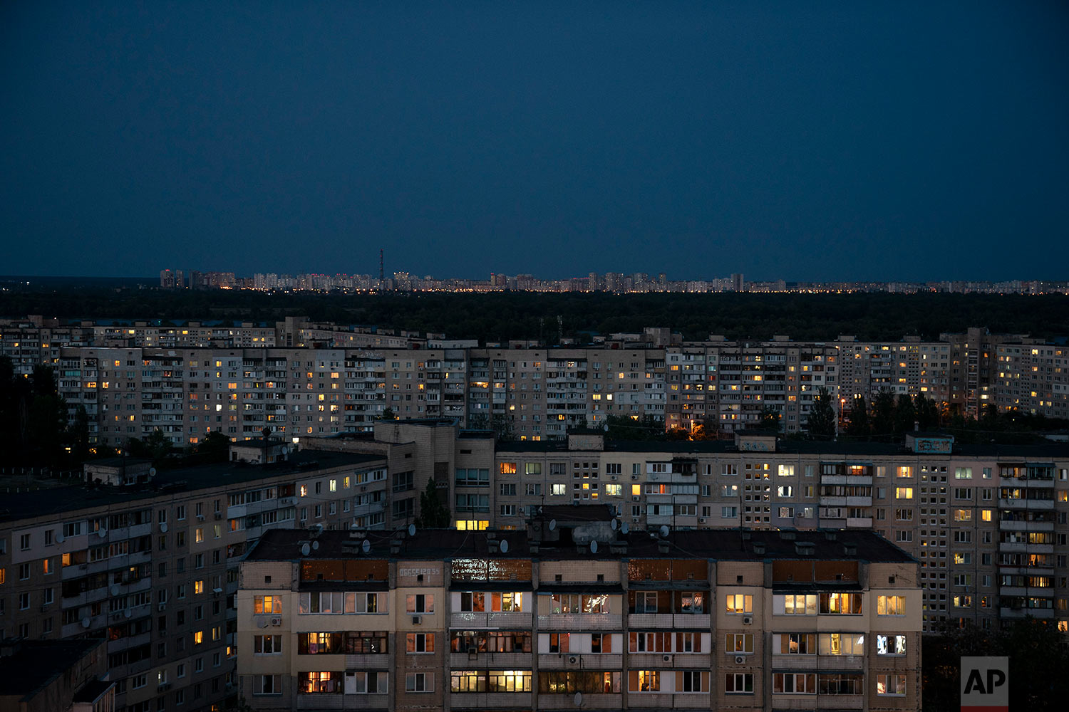 Buildings are illuminated at dusk In Kiev, Ukraine on Aug. 21, 2018. (AP Photo/Felipe Dana)