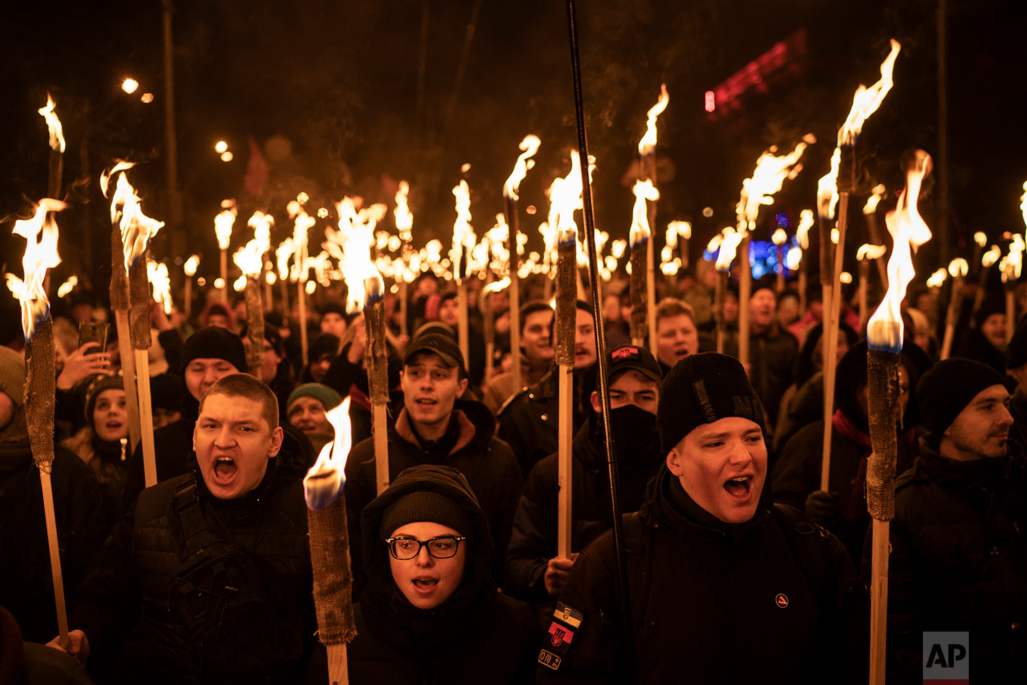 Nationalist carry torches during a rally to mark the birth anniversary of Stepan Bandera, founder of a rebel army that fought against the Soviet regime, in Kiev, Ukraine, Jan. 1, 2019. (AP Photo/Felipe Dana)