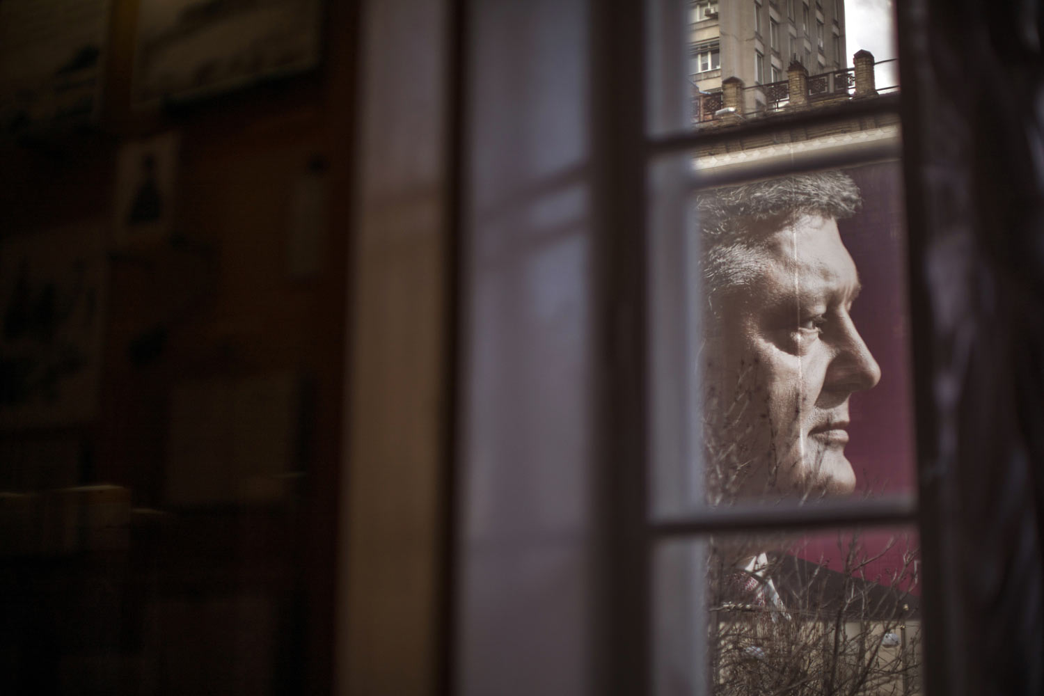 A large billboard with the face of Petro Poroshenko, president of Ukraine and candidate for 2019 elections, is seen through a window in central Kiev, Ukraine, Tuesday, March 26, 2019. Presidential elections are scheduled for March 31. (AP Photo/Emilio Morenatti)
