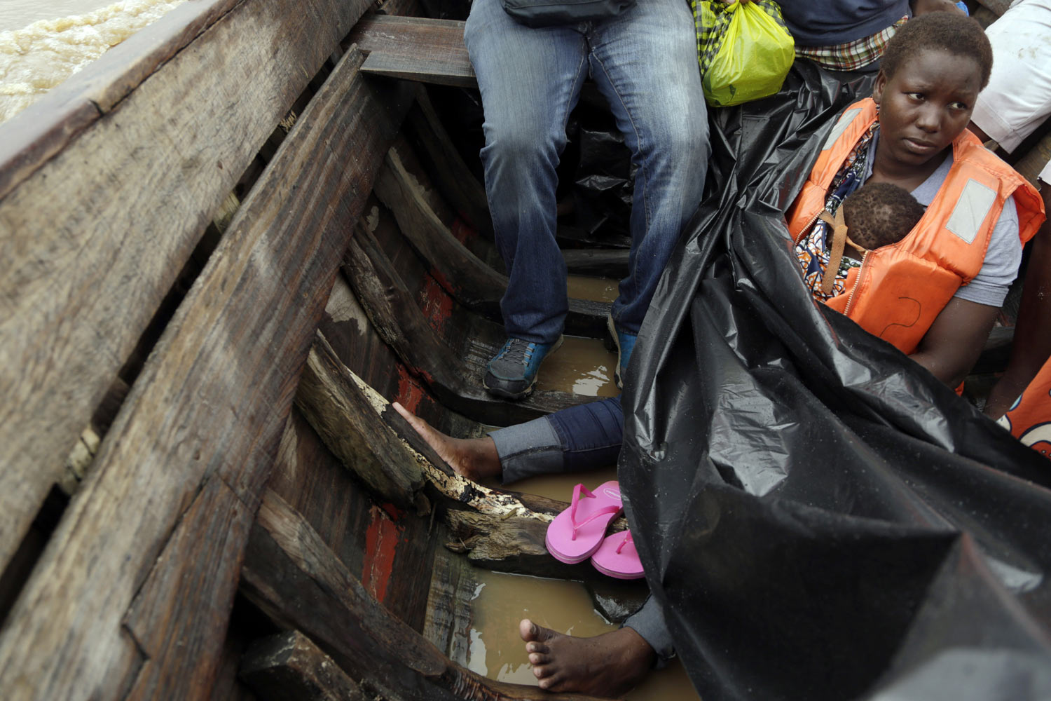 Veronica Fatia carries her 2-year-old daughter as they travel in a wooden boat to Buzi district, 200 kilometers (120 miles) outside Beira, Mozambique, on Saturday, March 23, 2019. They left the cyclone-shattered city of Beira for the town of Buzi, which for a week people had been fleeing to with little but their clothes. (AP Photo/Themba Hadebe)