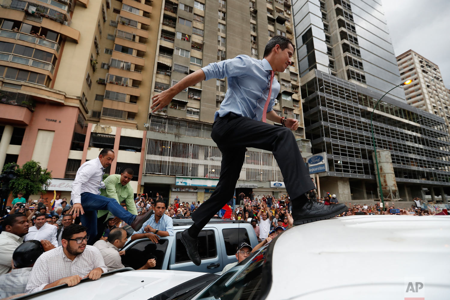 In this March 12, 2019 photo, National Assembly President Juan Guaido, who declared himself interim president of Venezuela, leaps on to a vehicle to speak to supporters as he visits different points of anti-government protest in Caracas, Venezuela.  (AP Photo/Eduardo Verdugo)