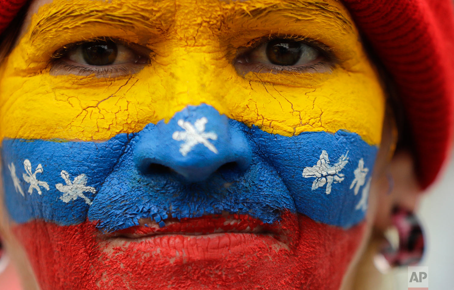 In this March 30, 2019 photo, her face painted in the colors of the national flag, a supporter of opposition leader Juan Guaido, Venezuela's self-proclaimed interim president, waits for his arrival in Los Teques, Miranda State, Venezuela. (AP Photo/Natacha Pisarenko)