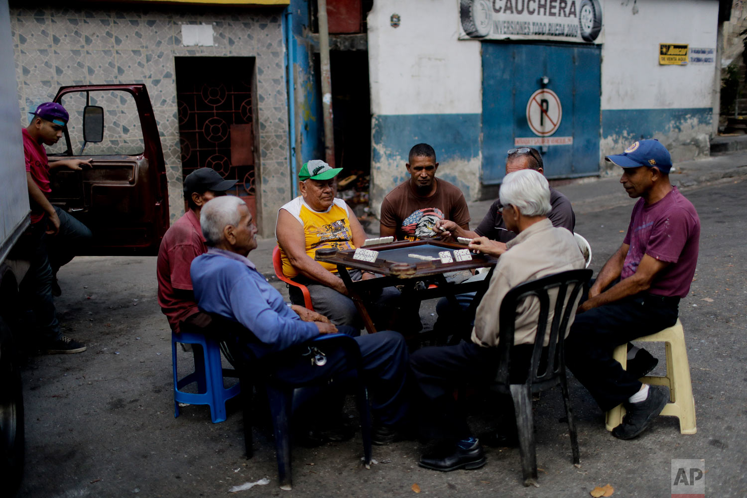 In this March 20, 2019 photo, men play dominos in a street in Caracas, Venezuela. (AP Photo/Natacha Pisarenko)