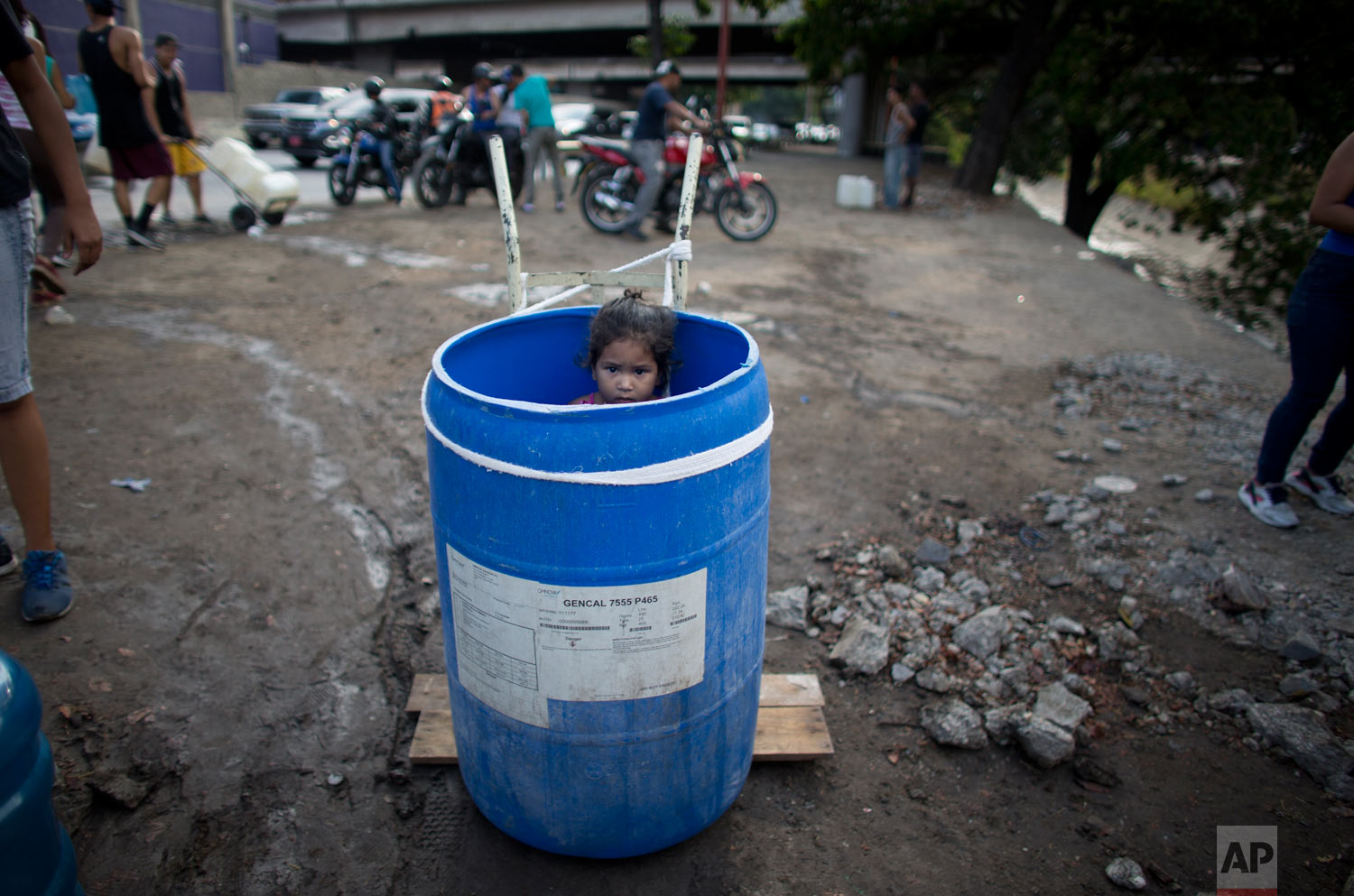 In this March 11, 2019 photo, a little girl stands inside a plastic barrel while her family waits to collect water from an open pipe above the Guaire River, during rolling blackouts which affect the water pumps in people's homes, offices and stores, in Caracas, Venezuela. (AP Photo/Ariana Cubillos)