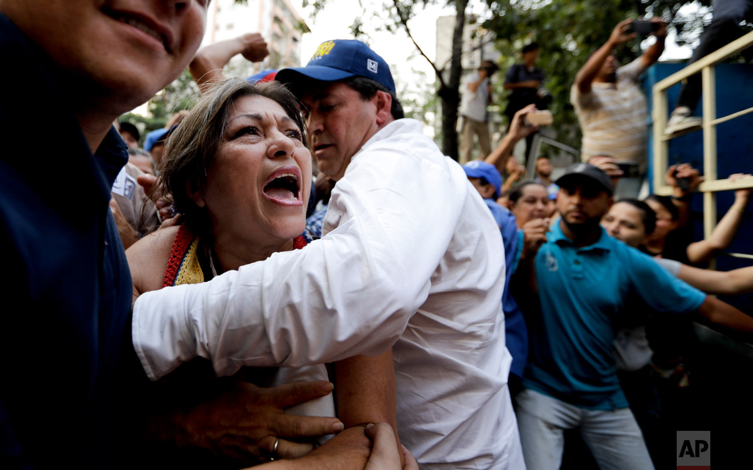 In this March 28, 2019 photo, a supporter of Venezuela's self-proclaimed interim president Juan Guaido is stopped as she tries to get near him during a rally in Caracas, Venezuela. (AP Photo/Natacha Pisarenko)