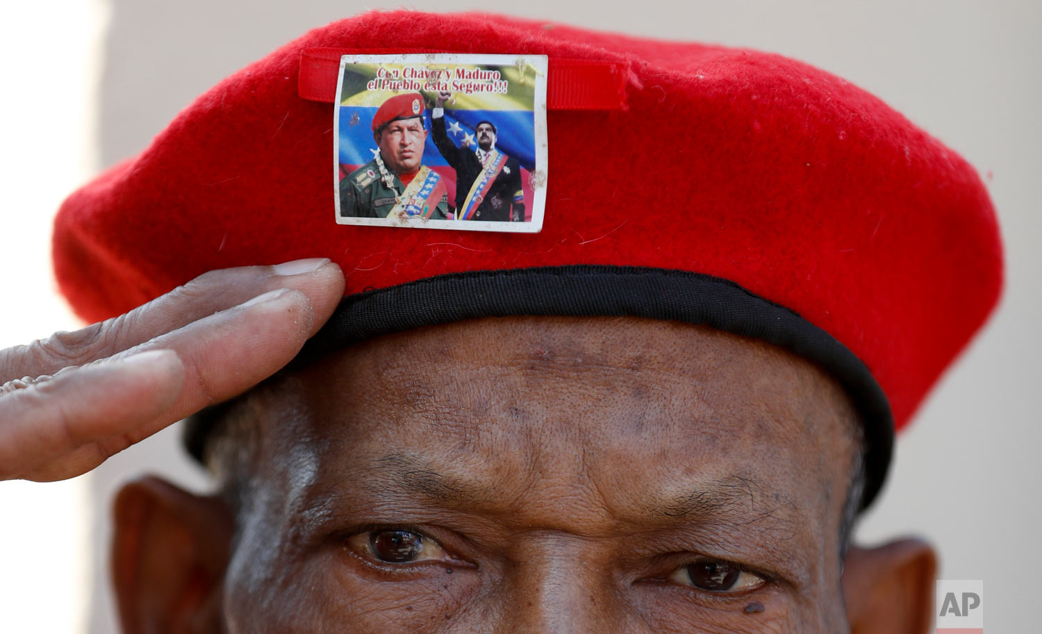 In this March 5, 2019 photo, a man wearing the iconic red beret of Venezuela's late President Hugo Chavez, featuring a photo of current President Nicolas Maduro with Chavez, salutes as he waits to enter the Historic Military Museum to visit the leader's remains on the sixth anniversary of his death in Caracas, Venezuela. (AP Photo/Eduardo Verdugo)