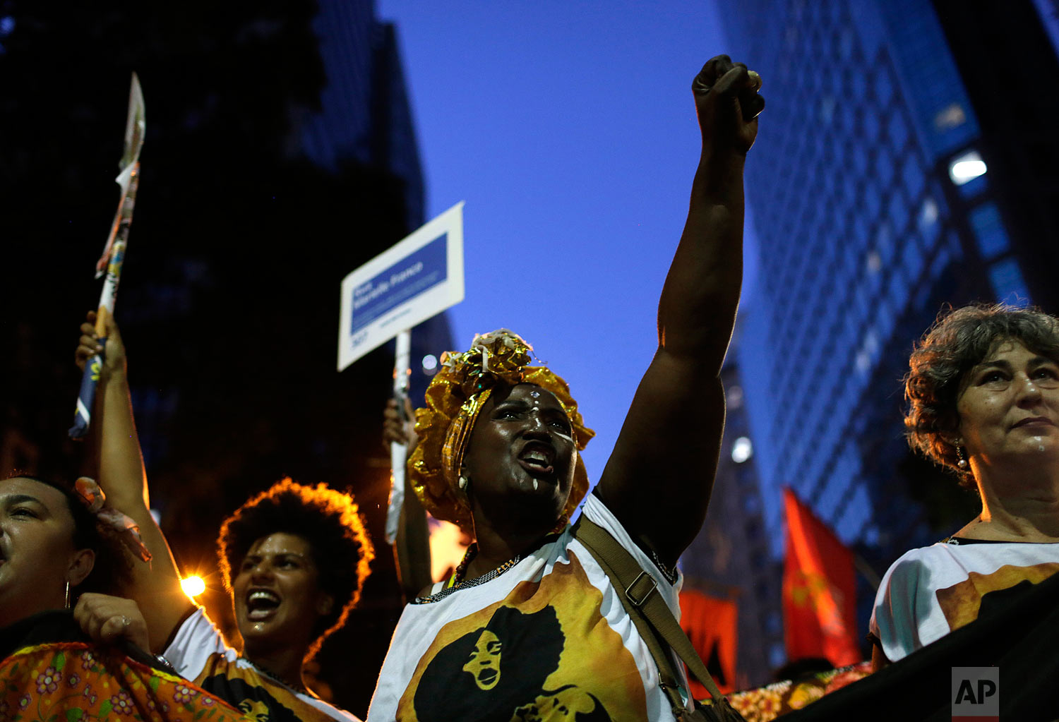 In this March 8, 2019 photo, women shout slogans during a march marking International Women's Day in Rio de Janeiro, Brazil. (AP Photo/Silvia Izquierdo)