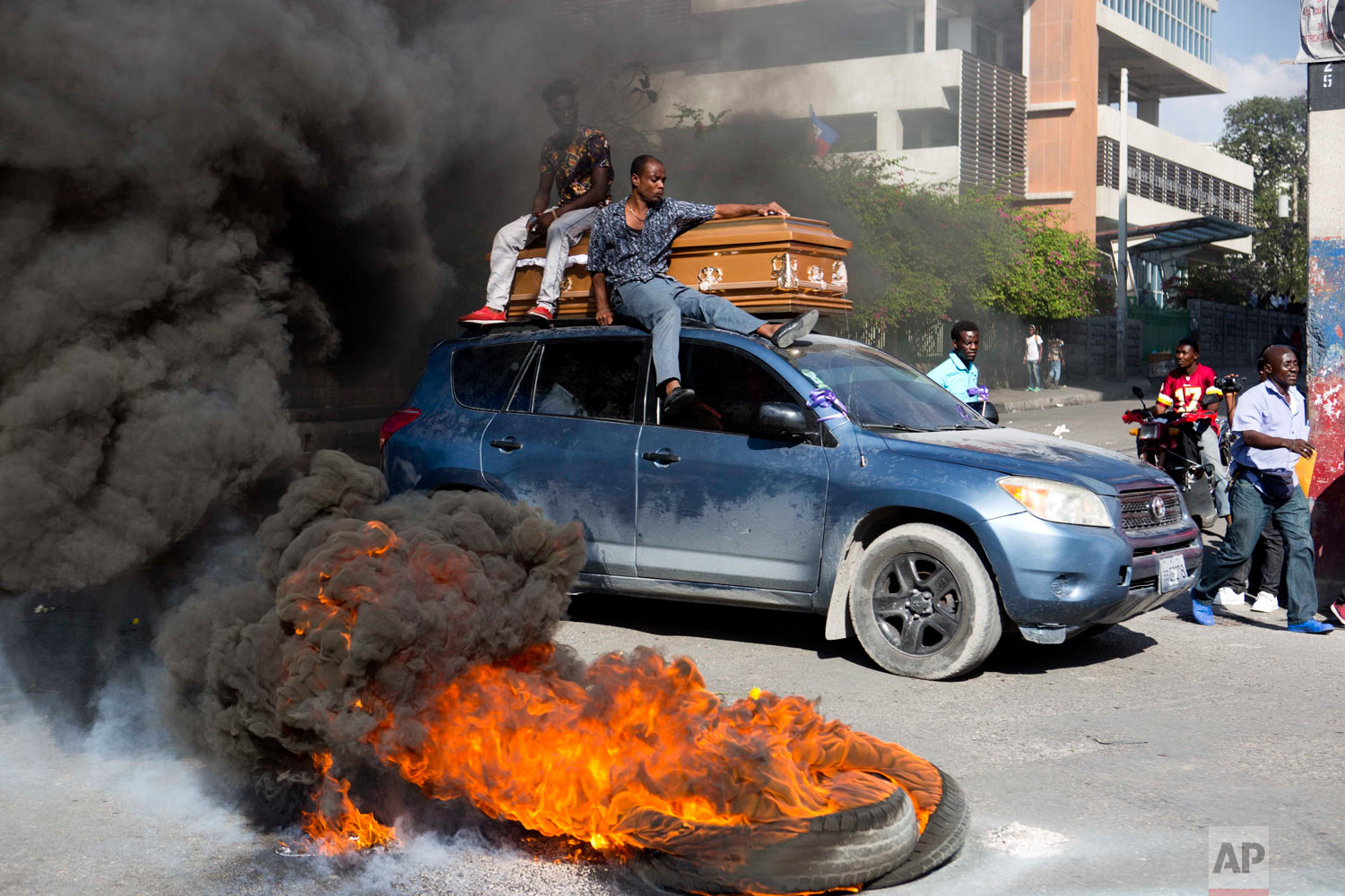 In this March 4, 2019 photo, a car carries a coffin containing the body of one of the demonstrators who was killed during previous protests in Port-au-Prince, Haiti. (AP Photo/Dieu Nalio Chery)
