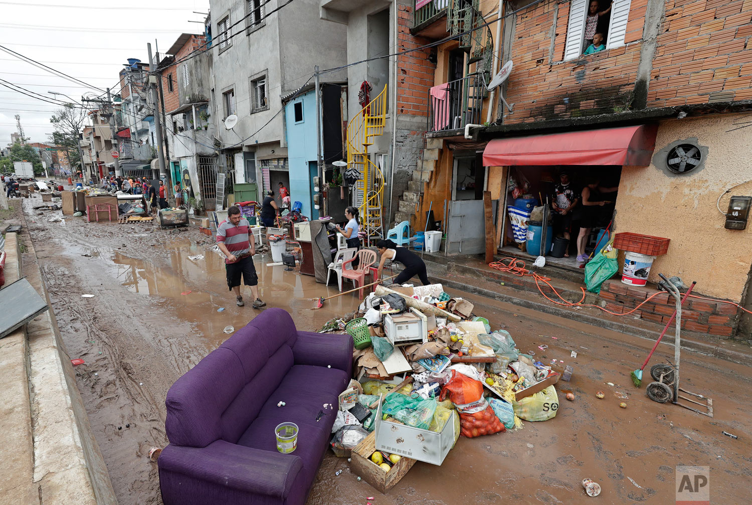 In this March 11, 2019 photo, damaged belongings, spoiled food and soaked furniture are piled up in the street to be taken away as trash after flooding in Sao Paulo, Brazil. (AP Photo/Andre Penner)