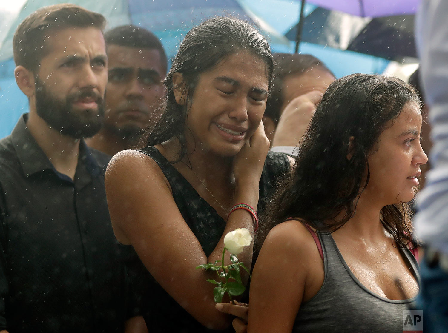 In this March 14, 2019 photo, a woman stands weeping in the rain during the burial of 15-year-old student Kaio Lucas da Costa Limeira, a victim of a mass shooting at the Raul Brasil State School in Suzano, Brazil. (AP Photo/Andre Penner)