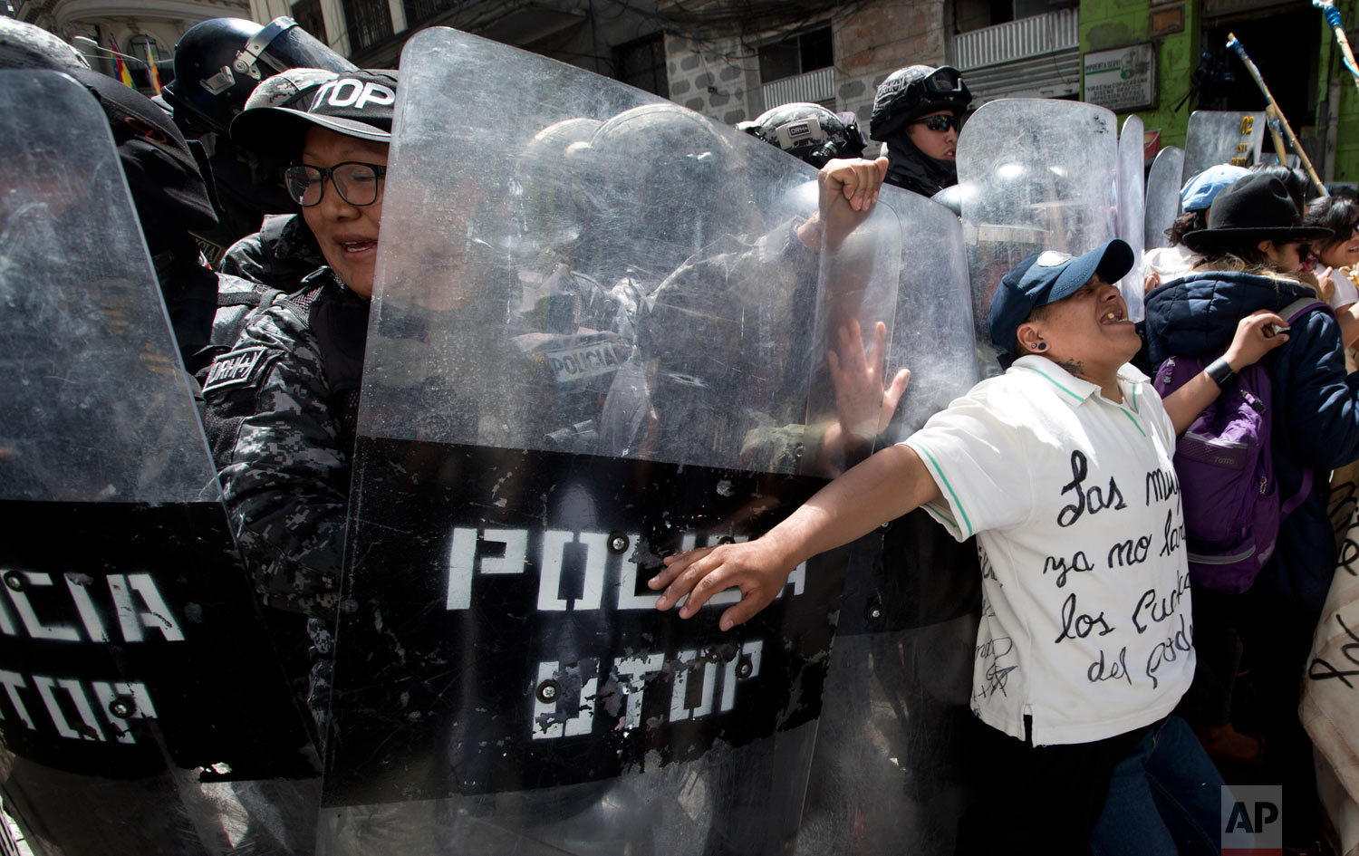 In this March 8, 2019 photo, a woman pushes against riot police who are preventing demonstrators from reaching government palace during a march marking International Women's Day, in La Paz, Bolivia. (AP Photo/Juan Karita)