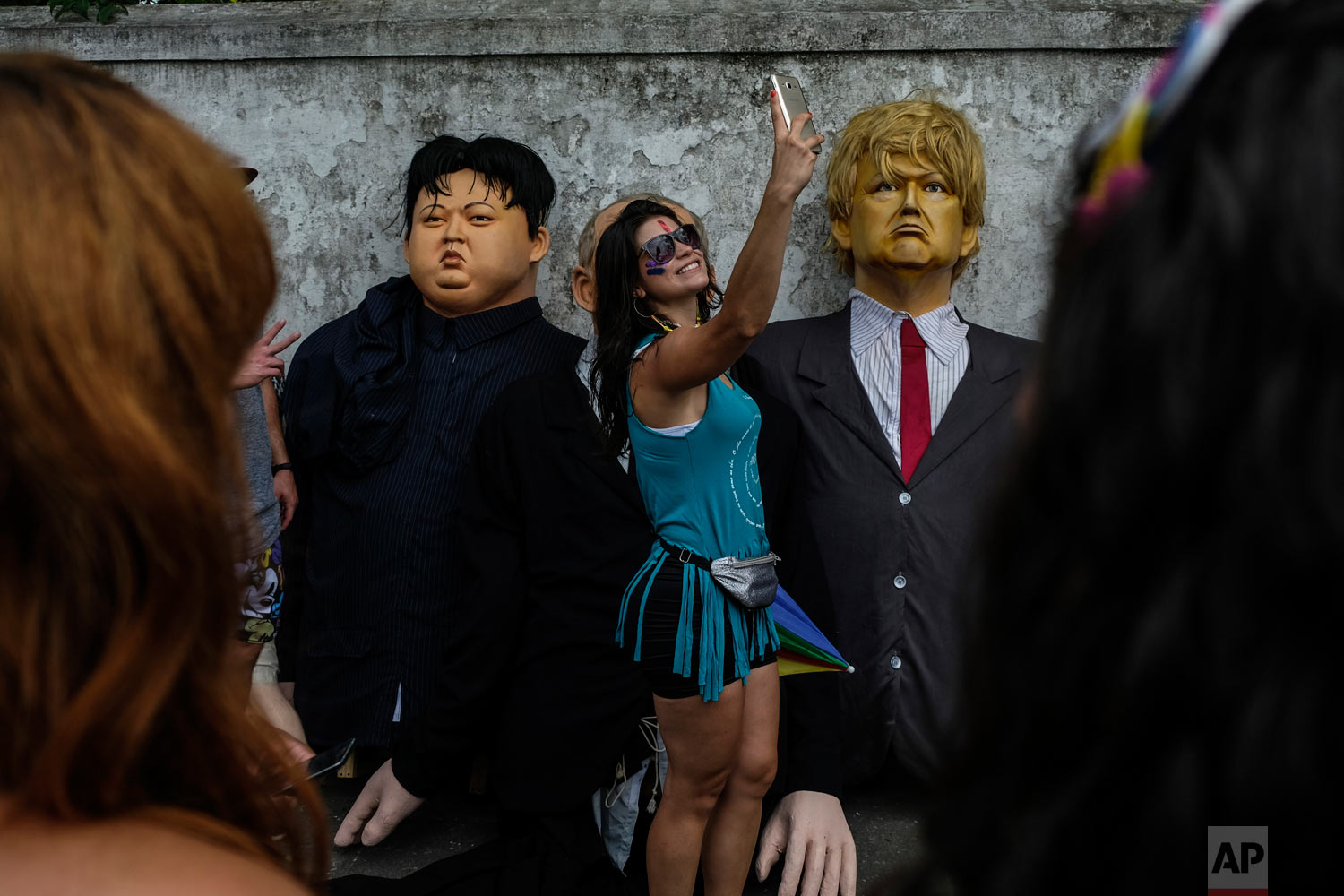 In this March 4, 2019 photo, a woman takes a selfie next to giant dolls depicting U.S. President Donald Trump, right, and North Korean leader Kim Jong-un, during carnival celebrations in Olinda, Pernambuco state, Brazil. (AP Photo/Diego Herculano)
