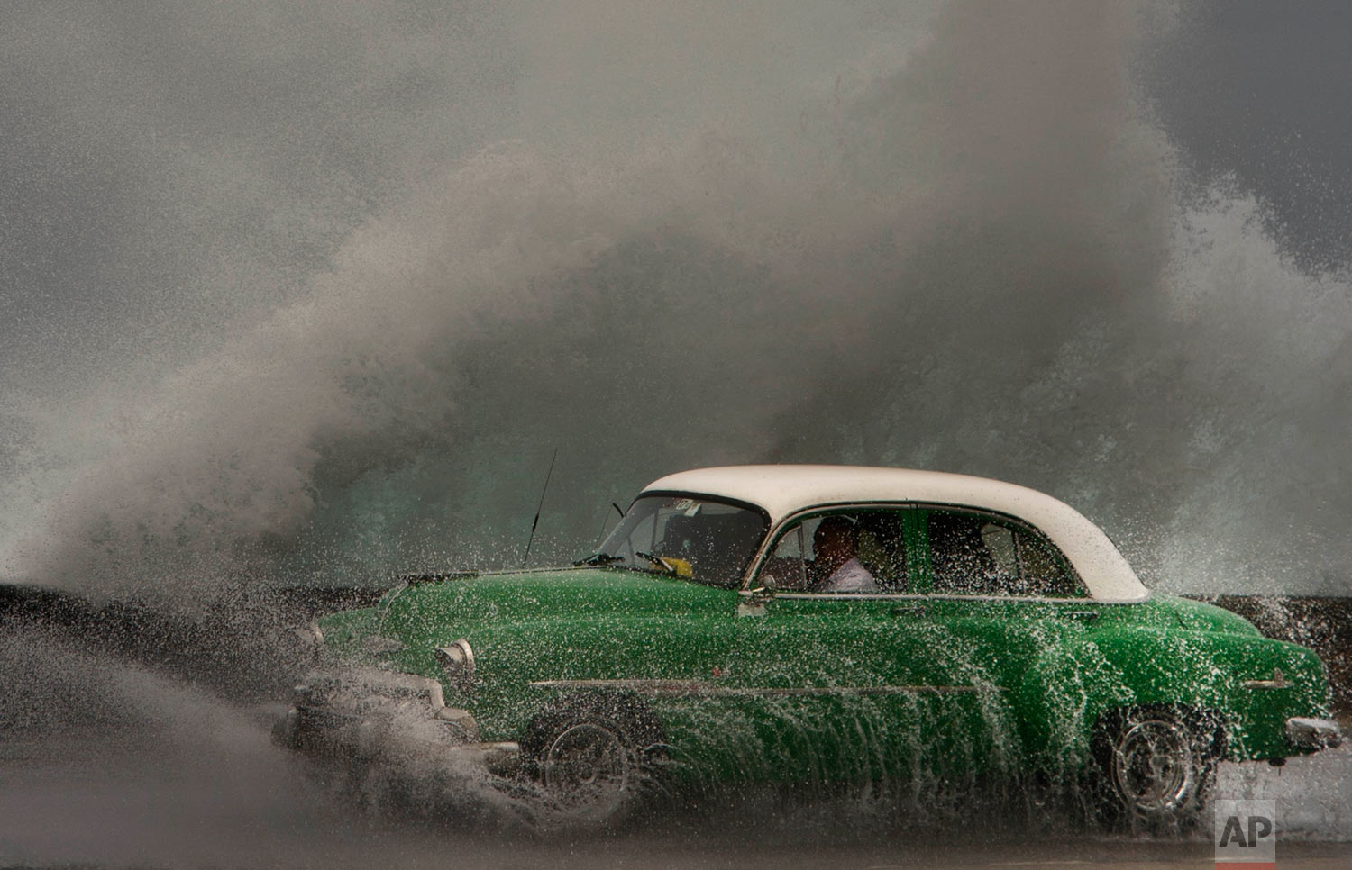 In this March 19, 2019 photo, waves crash against the Malecon sea wall as a taxi drives past in a classic American car in Havana, Cuba. (AP Photo/Ramon Espinosa)
