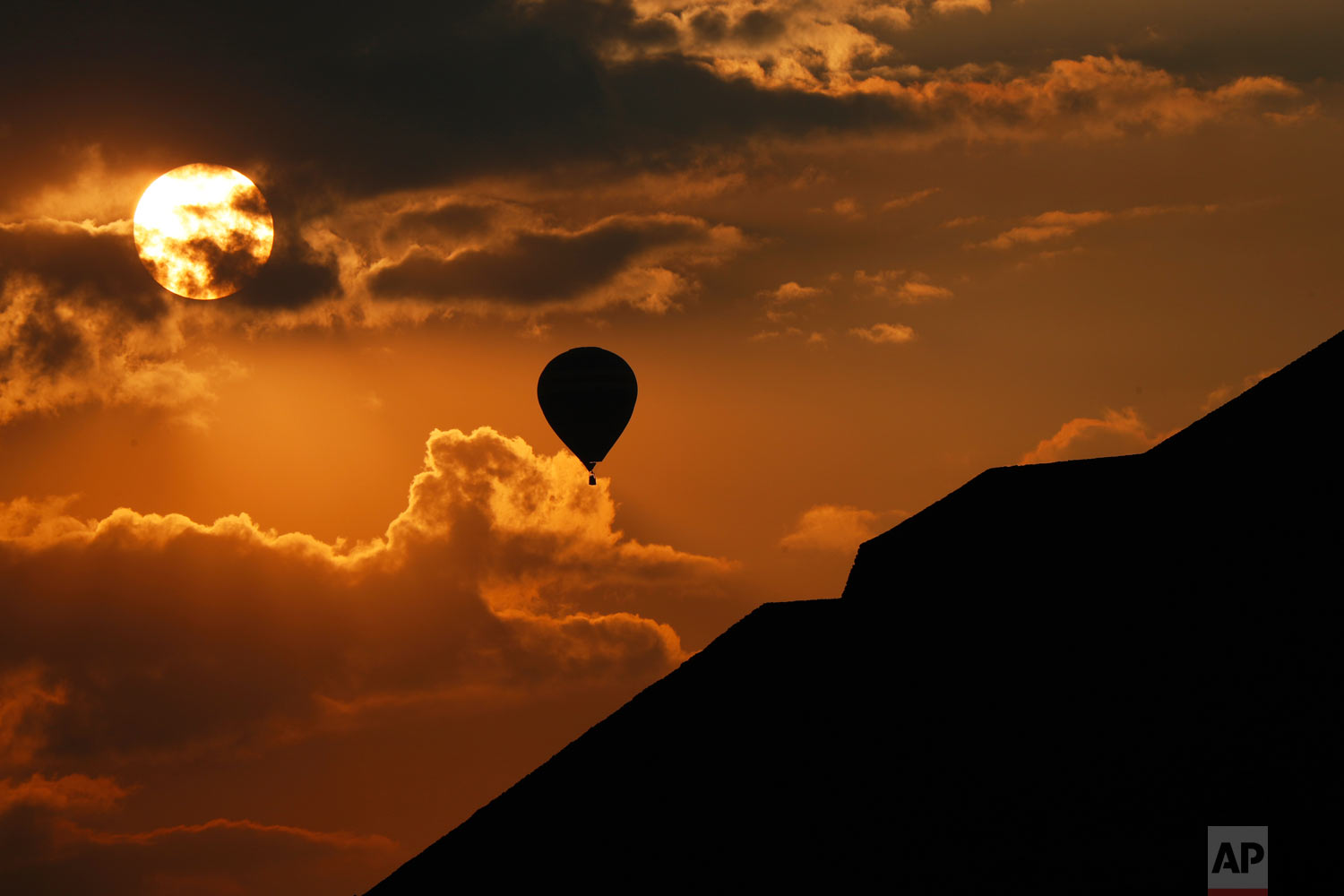 In this March 21, 2019 photo, a balloon flies near the Pyramid of the Sun in Teotihuacan, Mexico, on the Spring equinox. (AP Photo/Marco Ugarte)