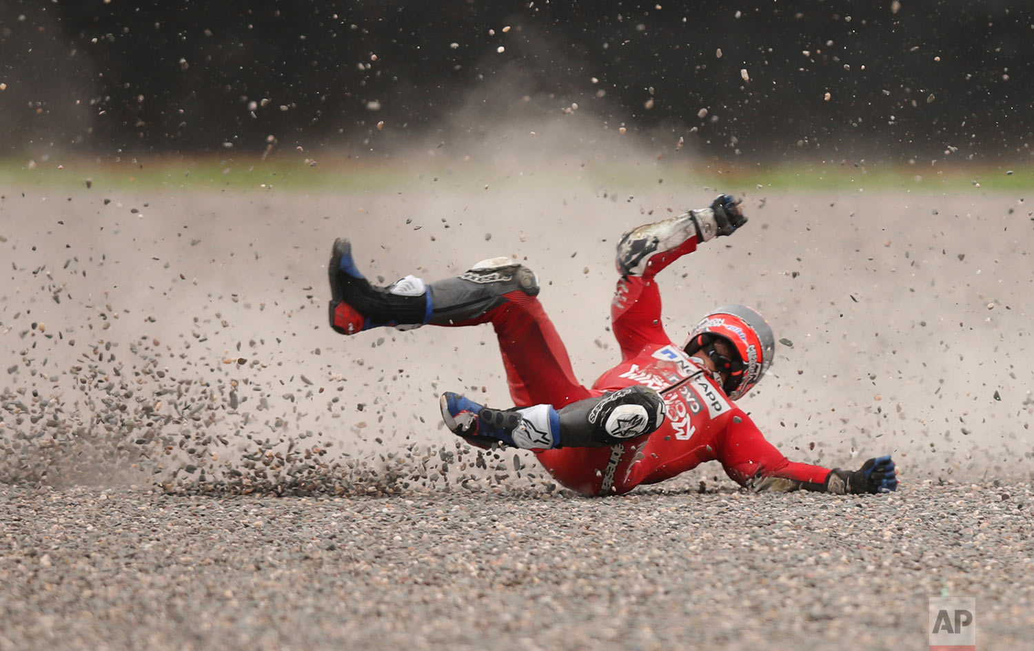 In this March 30, 2019 photo, Andrea Dovizioso of Italy falls from his bike during a Moto GP free practice run at the circuit in Termas de Rio Hondo, Argentina. Despite the fall Dovizioso raced in the third pole position on Sunday. (AP Photo/Nicolas Aguilera)