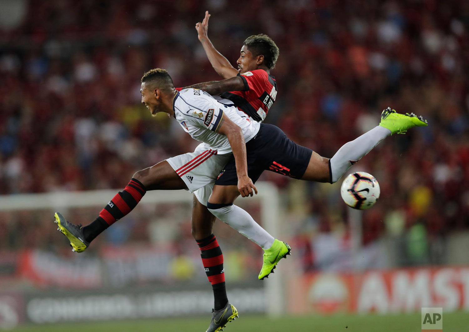 In this March 13, 2019 photo, Jose Quintero of Ecuador's Liga Deportiva Universitaria de Quito (white) fights for the ball with Bruno Henrique of Brazil's Flamengo during a Copa Libertadores soccer match at Maracana stadium in Rio de Janeiro, Brazil. (AP Photo/Silvia Izquierdo)