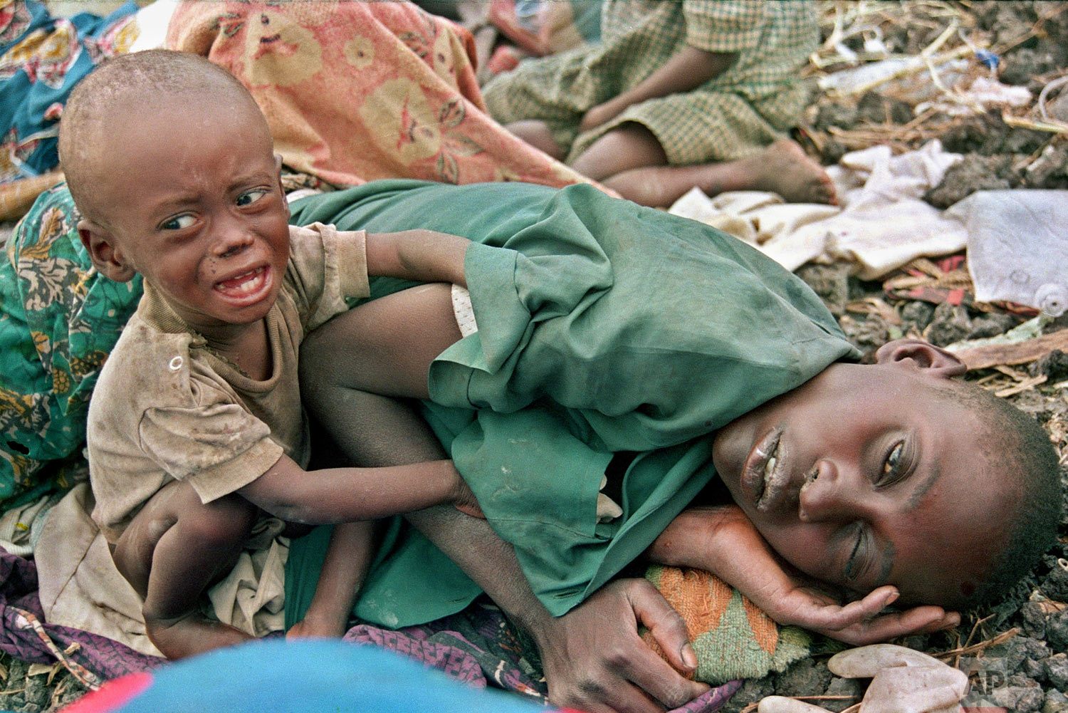 A Rwandan Hutu refugee child desperately tries to waken his mother from a diseased sleep in the Munigi camp outside Goma, in Zaire, now known as Congo on July 27, 1994. (AP Photo/Javier Bauluz)