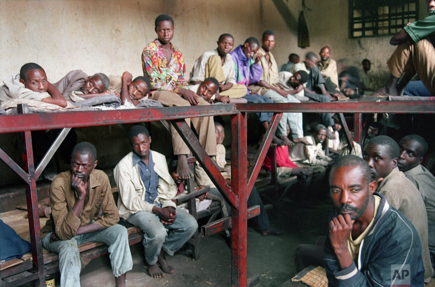 Some of the 334 inmates in a prison who are accused of committing war crimes and participating in the genocide, sit in the prison in Kibungo, Rwanda on Aug. 17, 1994. (AP Photo/Javier Bauluz)
