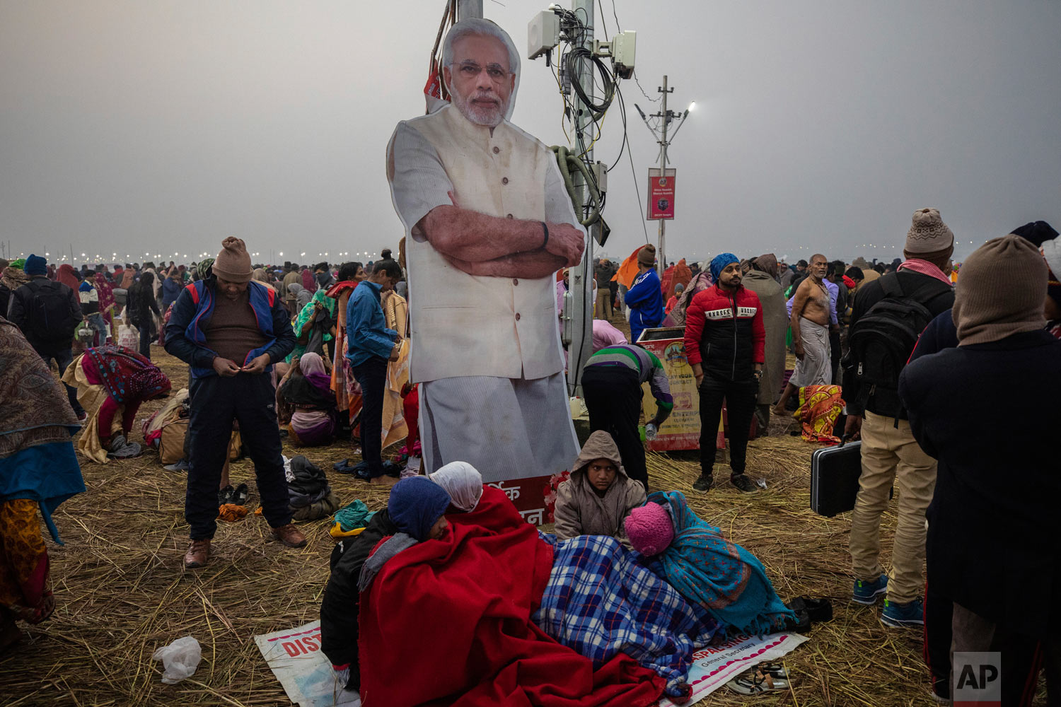 People stand near a poster of Prime Minister Narendra Modi during the Kumbh Mela festival in Allahabad, India, Jan. 14, 2018. (AP Photo/Bernat Armangue)