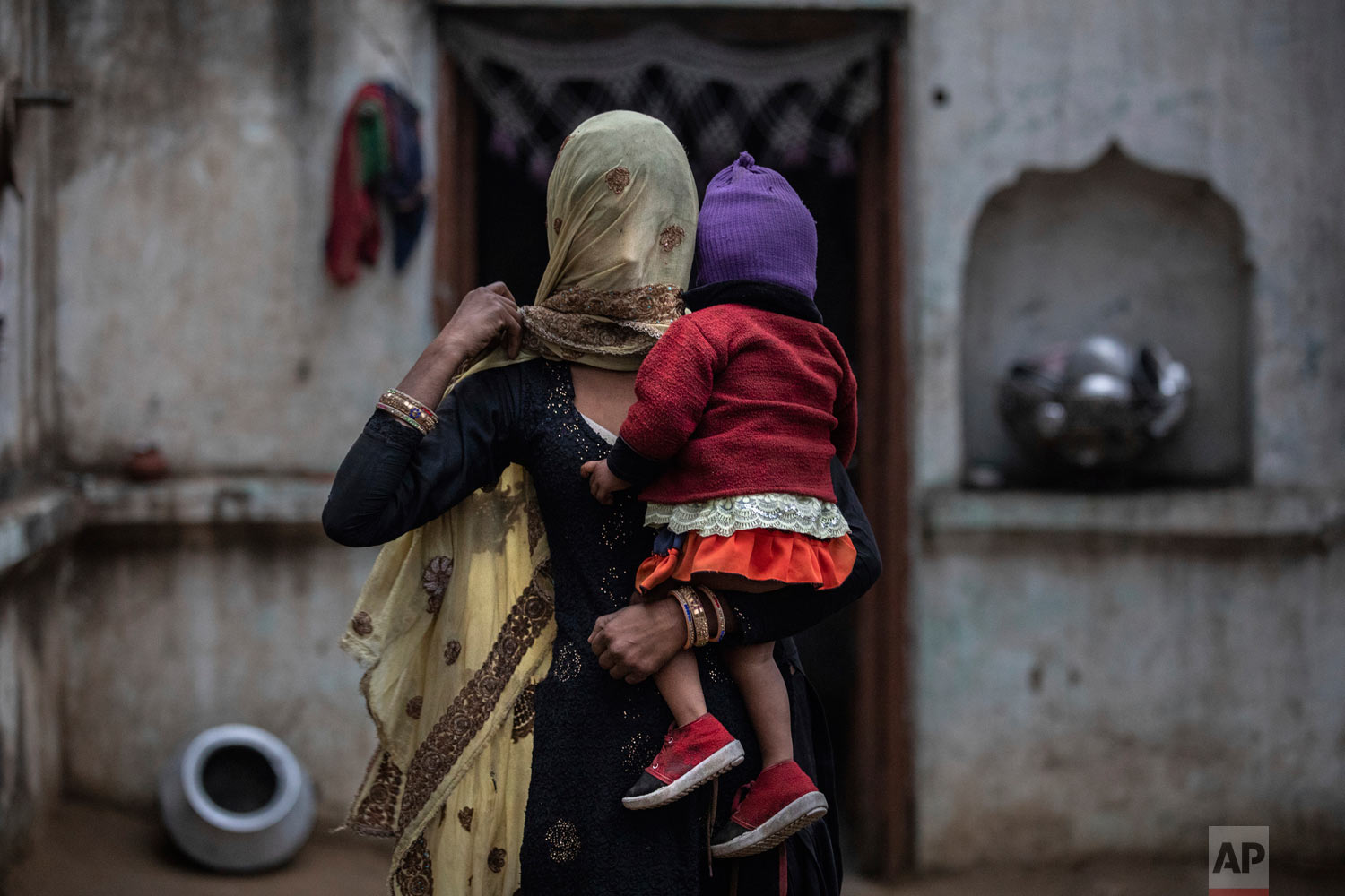 The wife of Saghir Khan, Anisa Khan, holds their daughter, Alfisa, at the family's house in Mirzapur, Jan. 22, 2019, Saghir was beaten by a group of Hindus after being spotted transporting cows. (AP Photo/Bernat Armangue)
