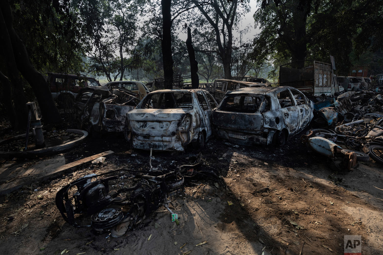 Vandalized cars and other vehicles sit in Chingarwathi, near Bulandshahr, in the northern Indian state of Uttar Pradesh, Dec. 4, 2018. (AP Photo/Bernat Armangue)
